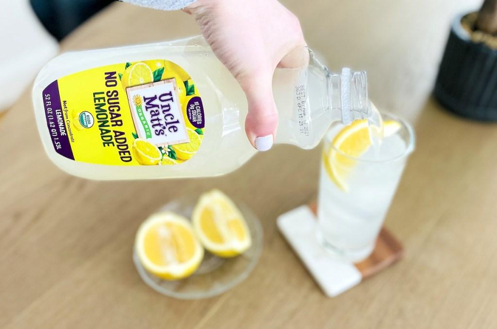 hand pouring keto sugar free lemonade into tall glass with fresh lemon