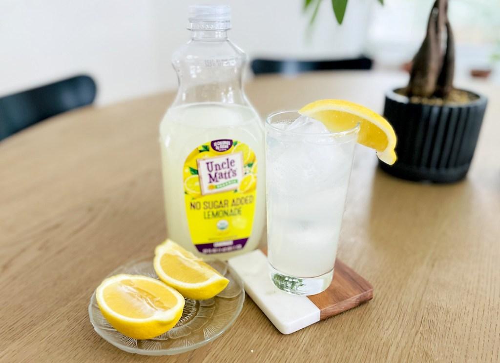 uncle matt lemonade with fresh lemon in glass sitting on wood table