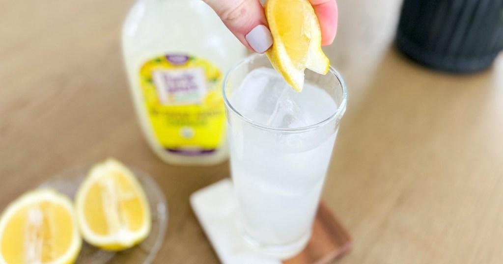 hand squeezing fresh lemon into glass of sugar free lemonade