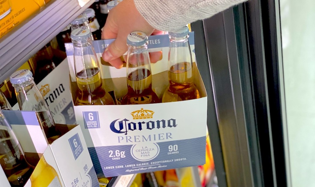 hand pulling pack of corona low-carb beer out of the fridge