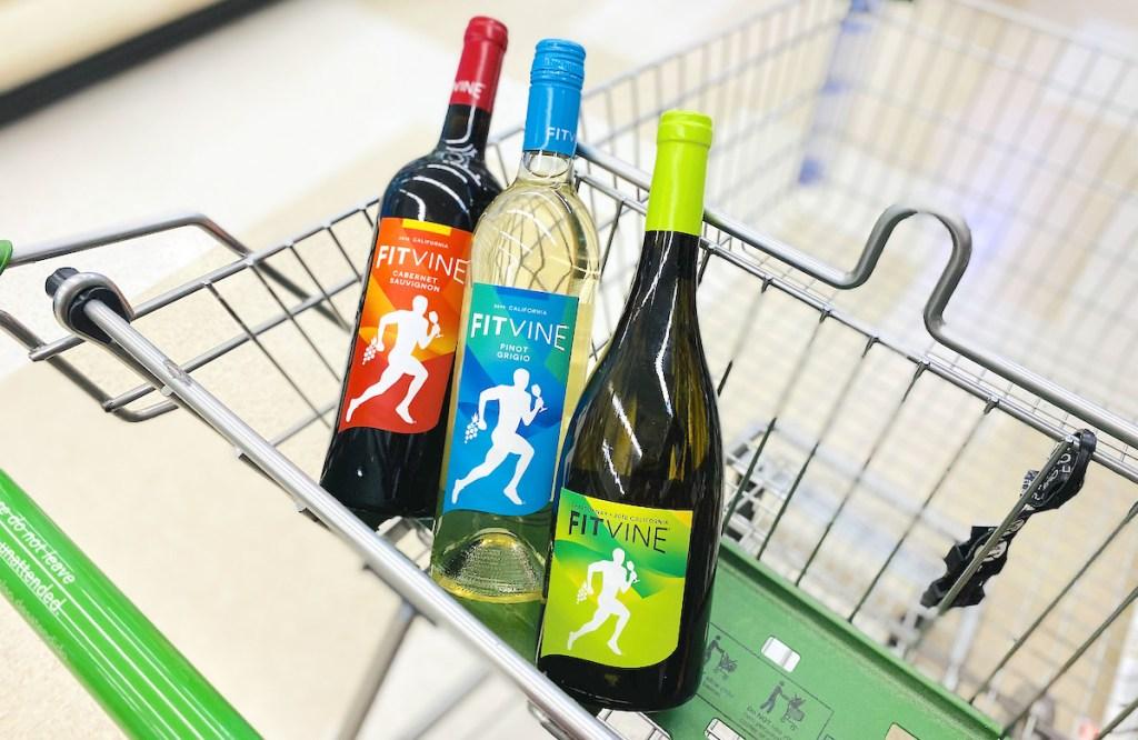three bottles of wine in top of grocery cart