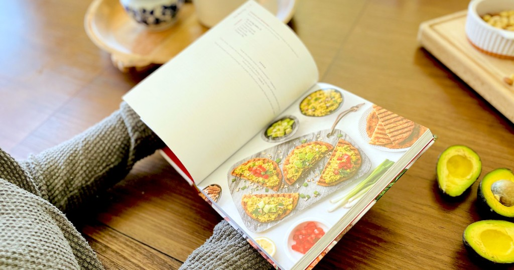 person holding keto cookbook with pita recipe on paper