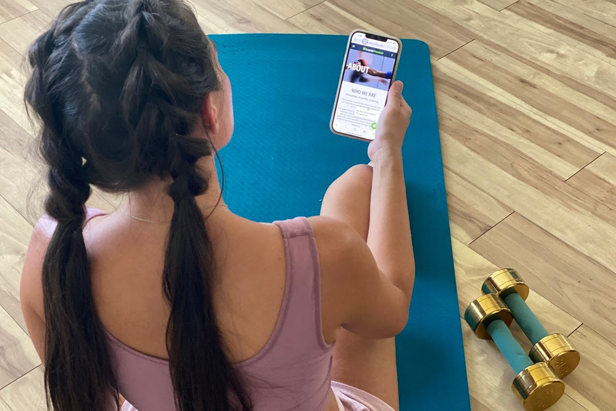 womansitting on mat and holding phone with inside tracker app