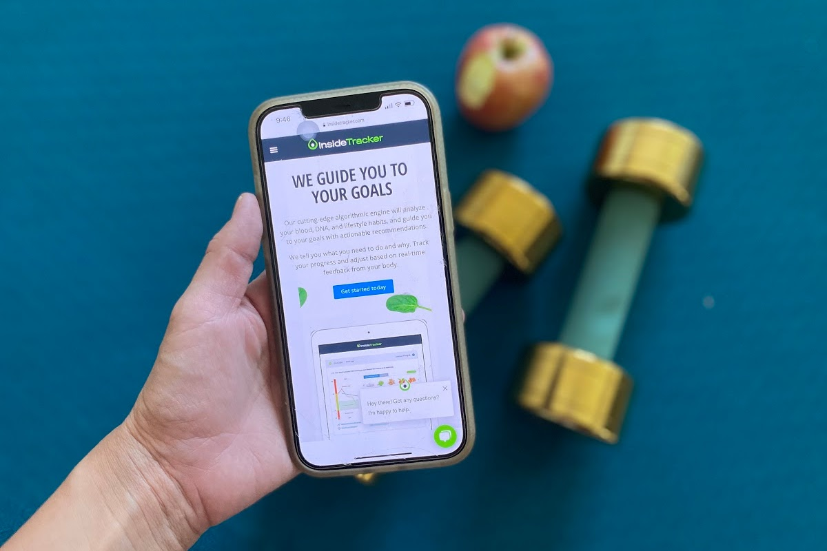 hand holding phone with InsideTracker app in front of dumbbells