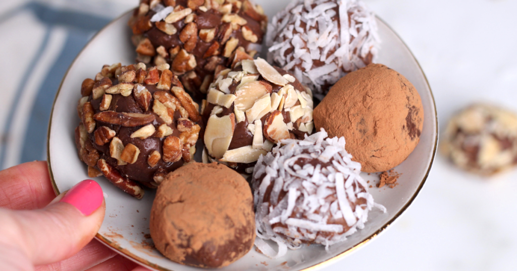 plate of keto chocolate truffles with nuts and coconut