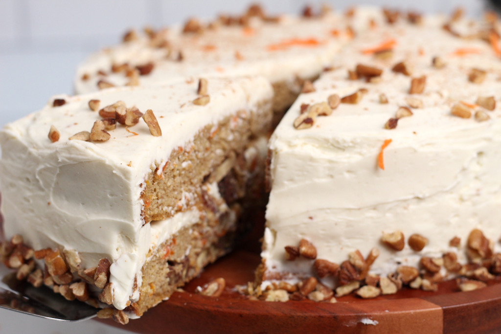 taking slice out of keto carrot cake with cream cheese frosting