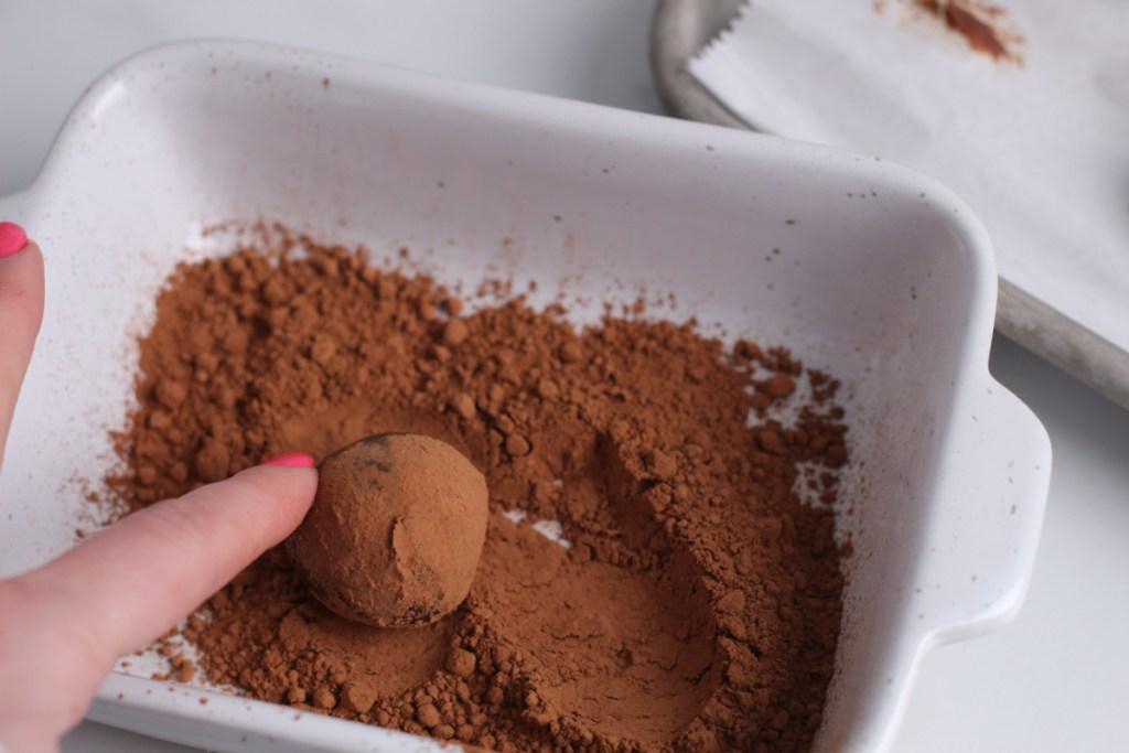 rolling keto chocolate truffle in cocoa powder
