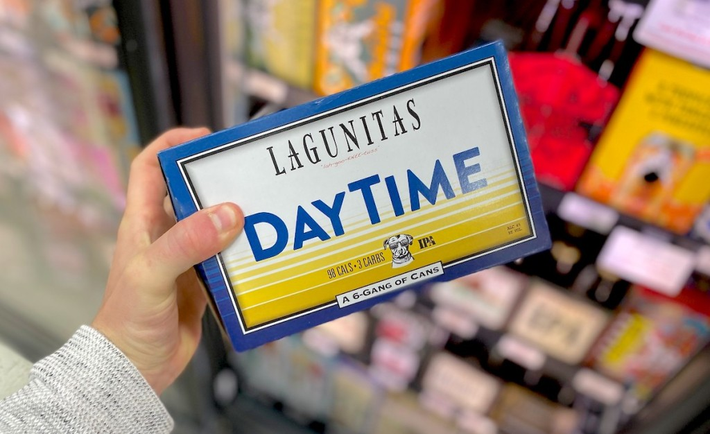 hand holding a pack of lagunitas daytime beer in front of fridge