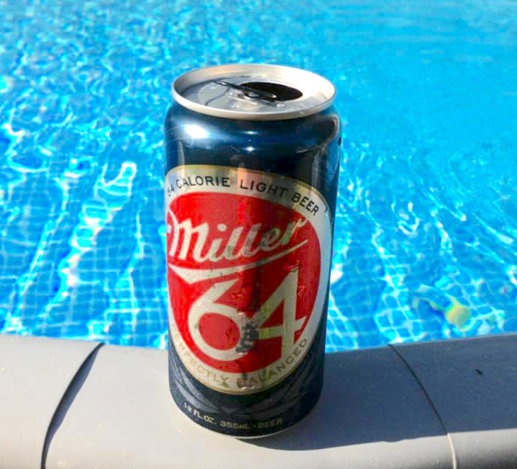 open can of miller 64 beer sitting on pool ledge
