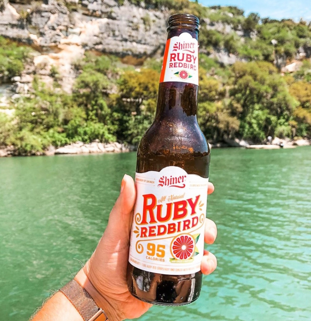 hand holding a glass bottle of shiner ruby redbird low-carb beer in front of blue lake