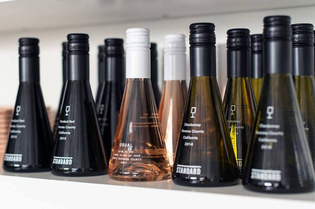 row of unique shaped bottles on white shelf