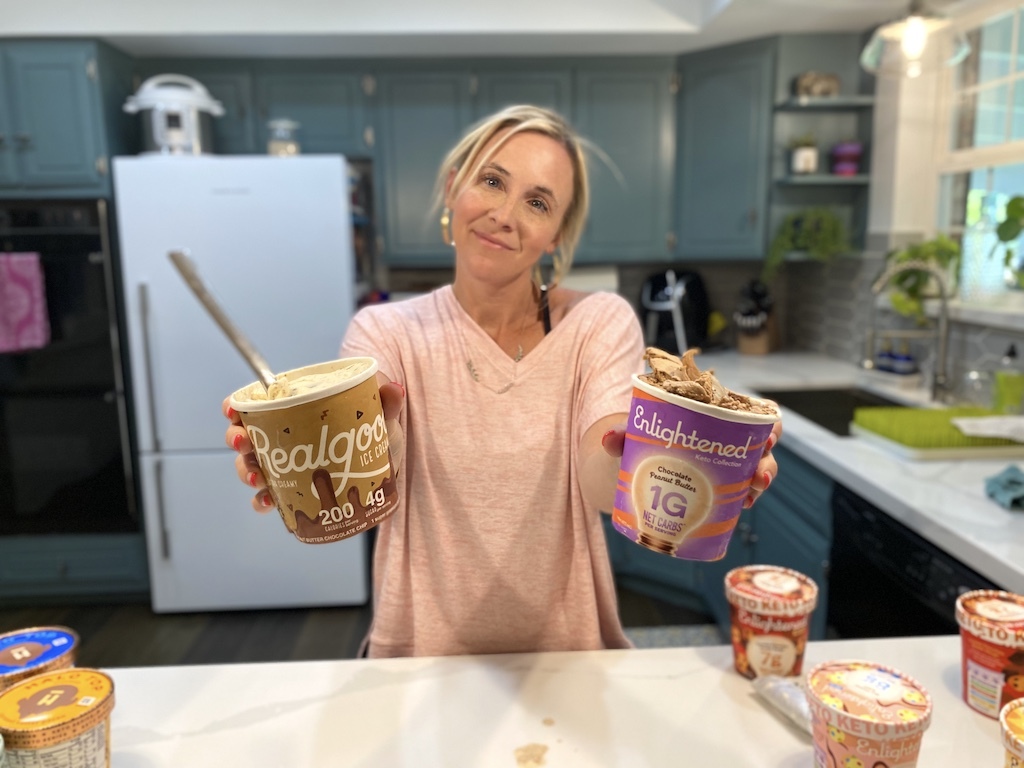 woman holding pints of keto ice cream in each hand in kitchen