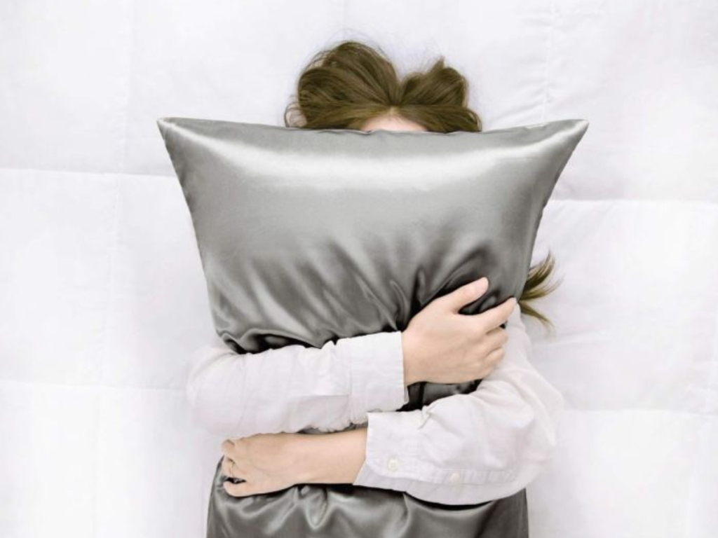 woman covering face with pillow