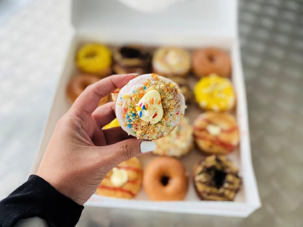 holding a mini-doughnut