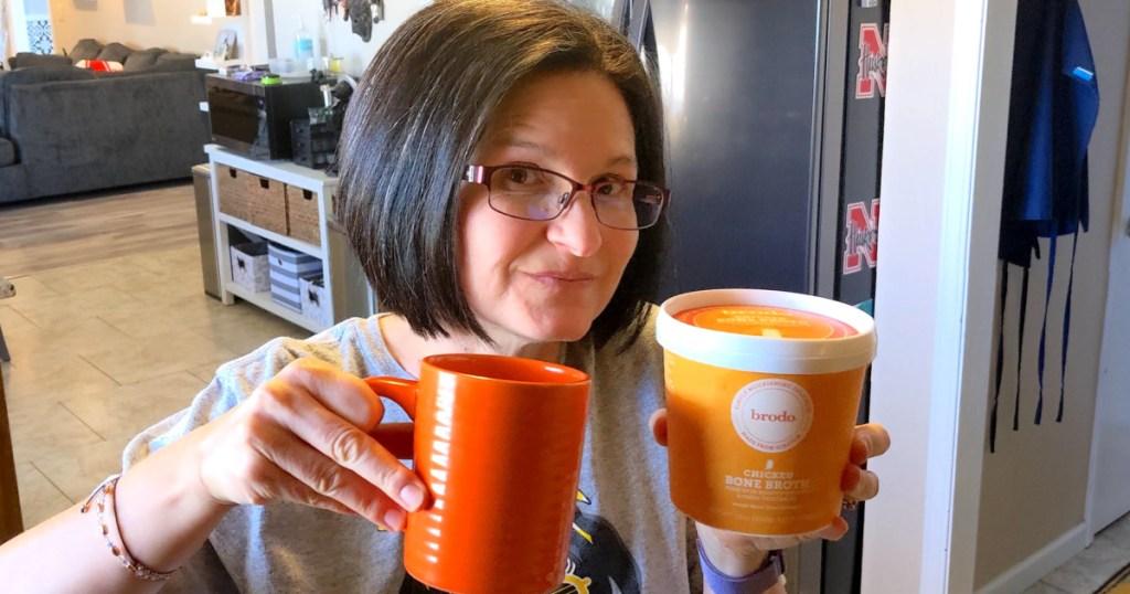 woman holding Brodo chicken bone broth with coffee mug