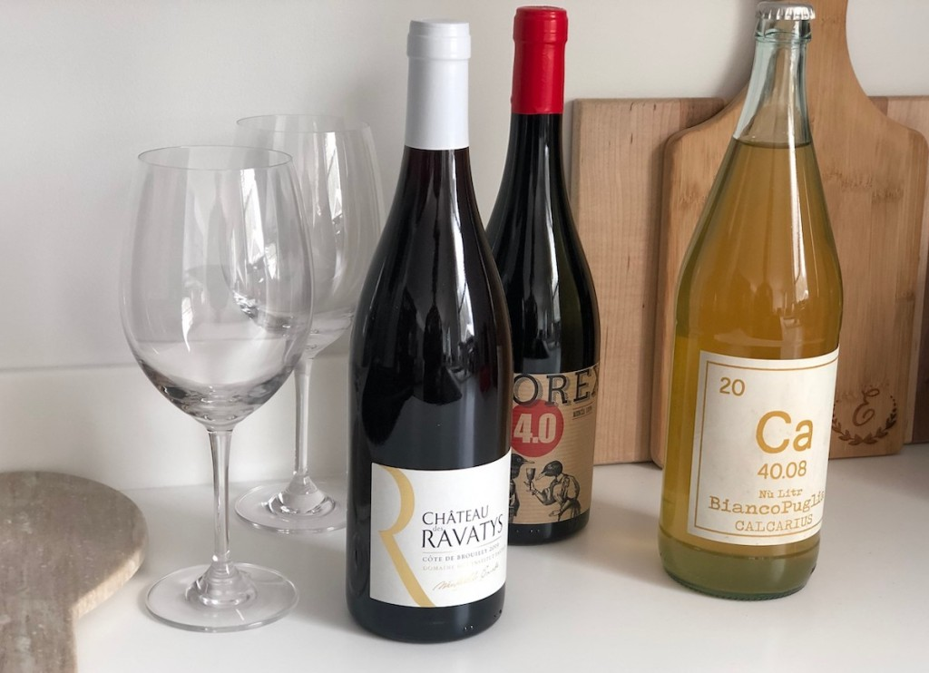 bottles of red and white wines with glasses on kitchen counter