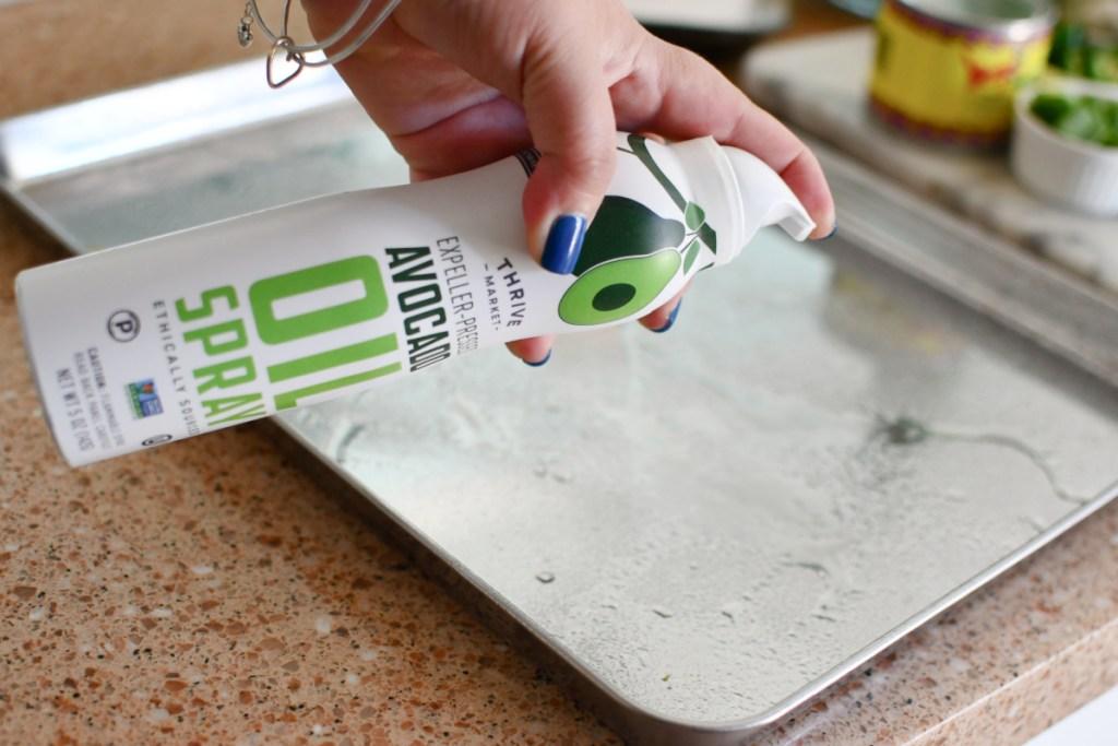 spraying sheet pan with avocado oil