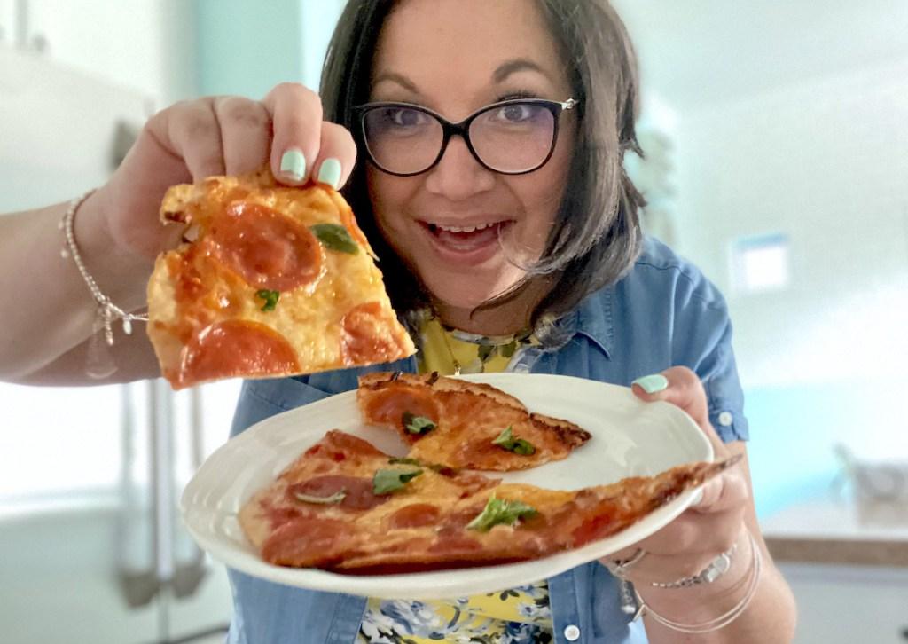 woman holding up slice of keto pepperoni basil pizza