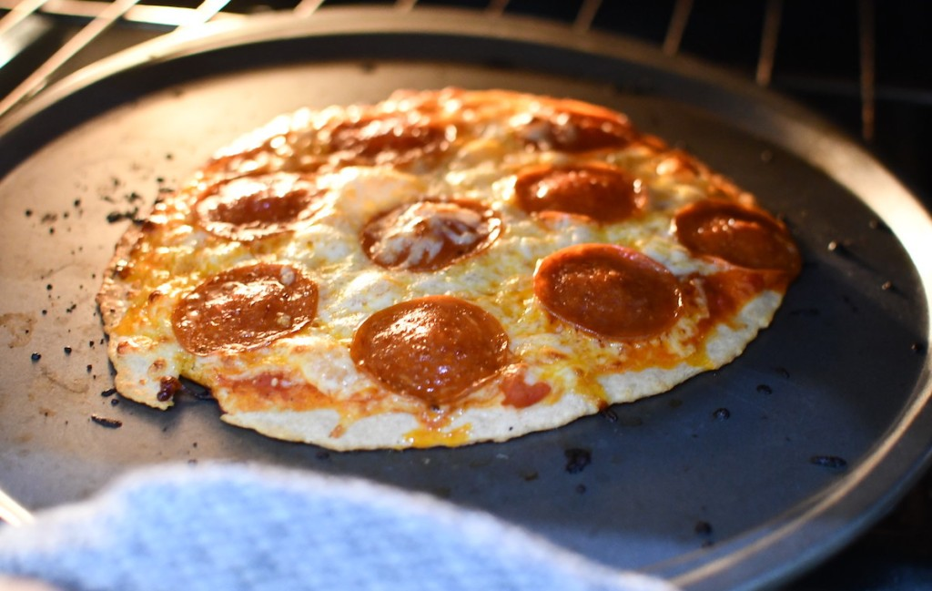 pepperoni pizza baking in oven on round sheet pan
