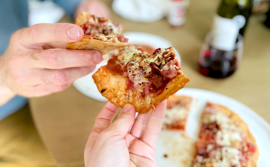 two people putting slices of pizza together