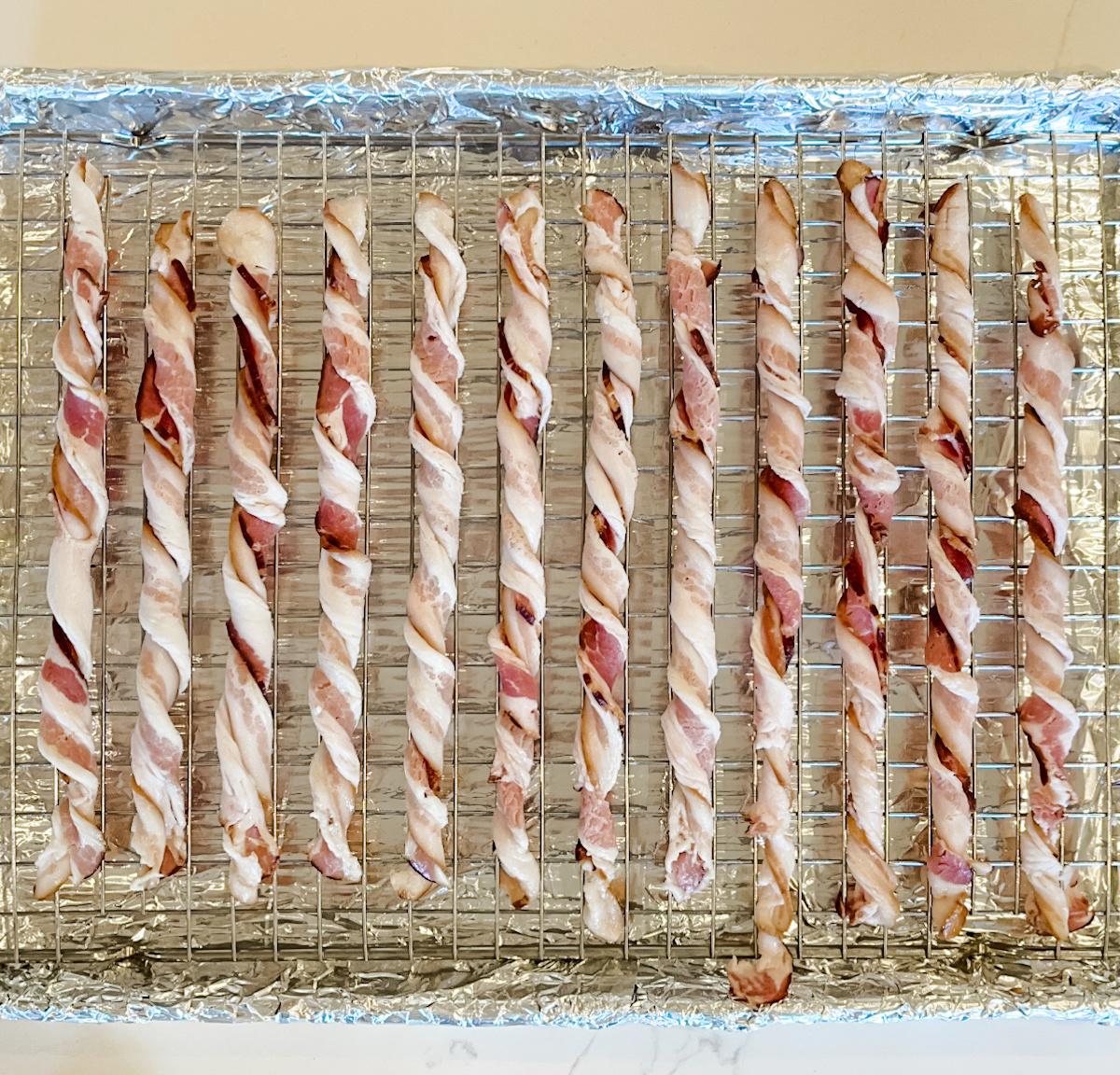 raw bacon twisted on wire rack