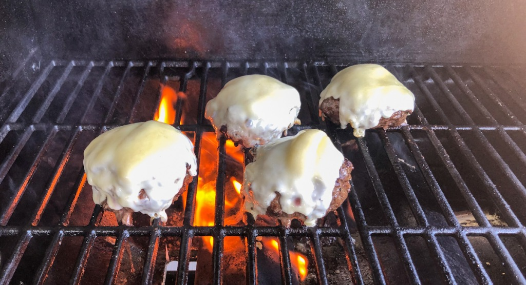 cheese melting on burgers on grill