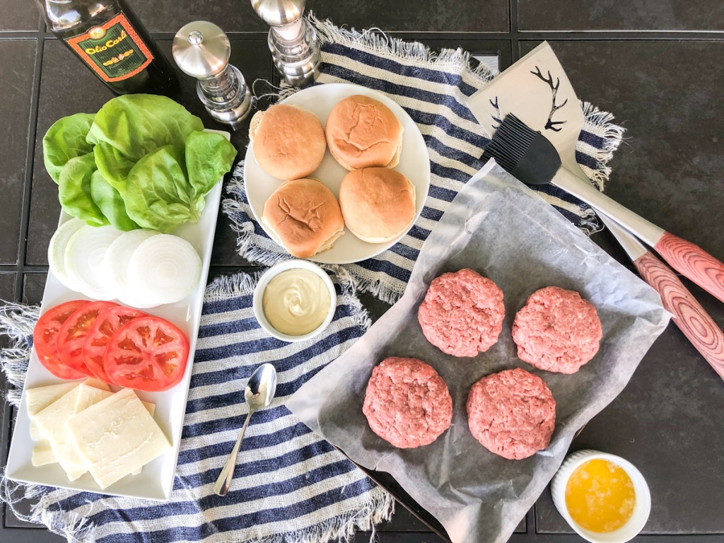 raw burgers ready to grill and toppings
