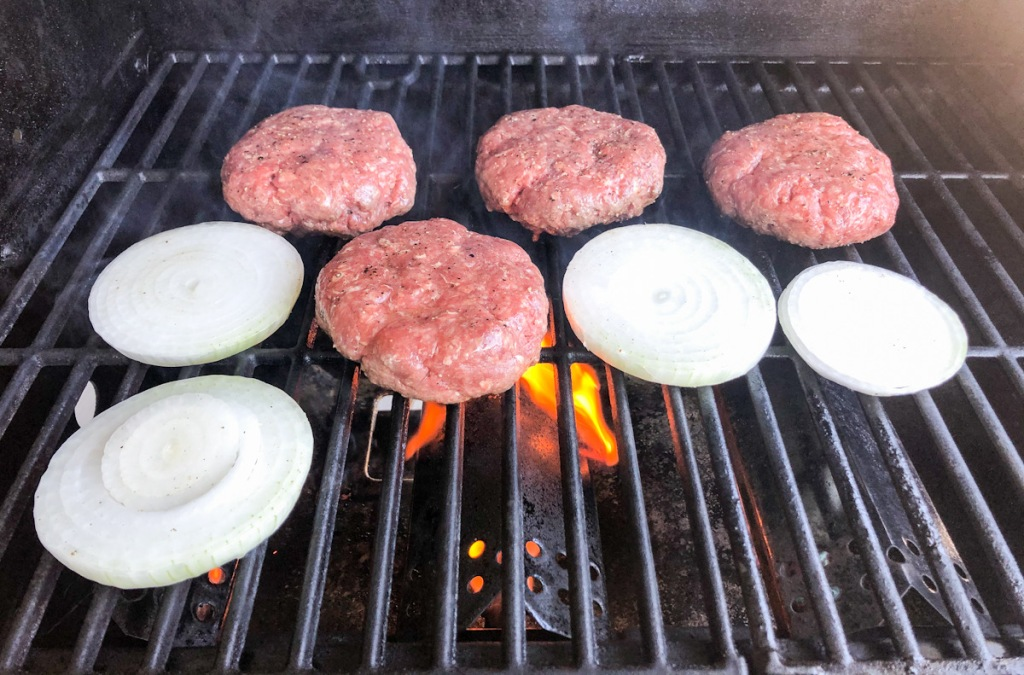 Burgers and onions on grill