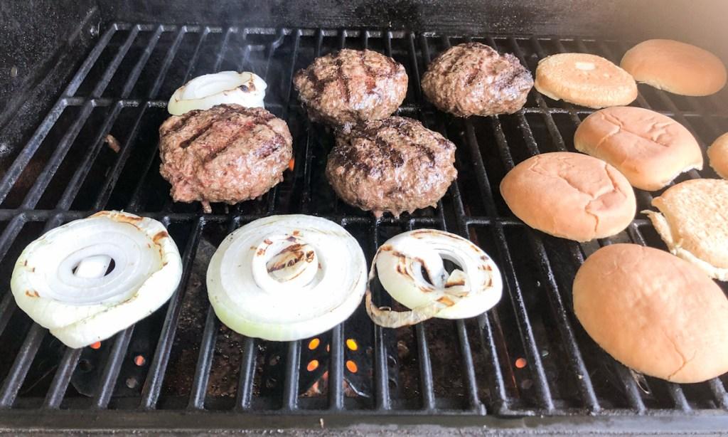 Hamburger patties, onions, and buns on grill