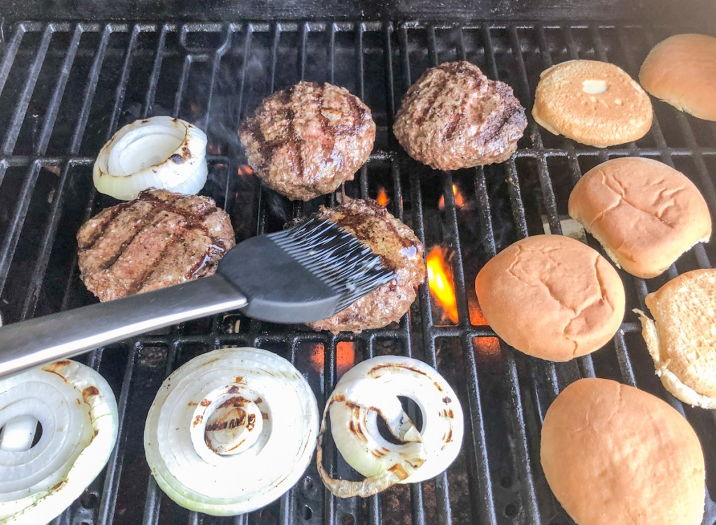 Basting burgers on grill