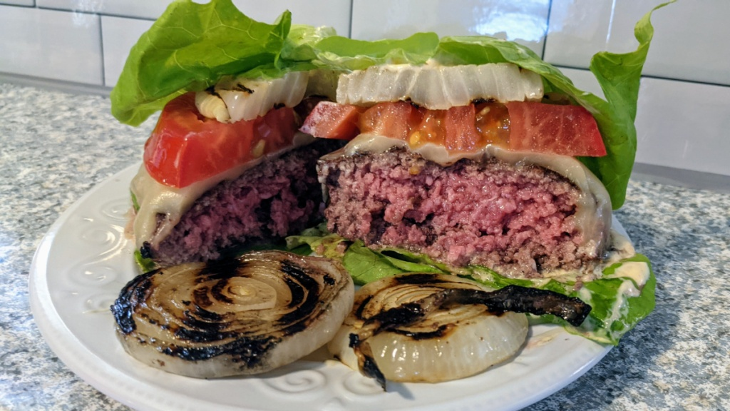 lettuce wrapped burger cut in half on a plate