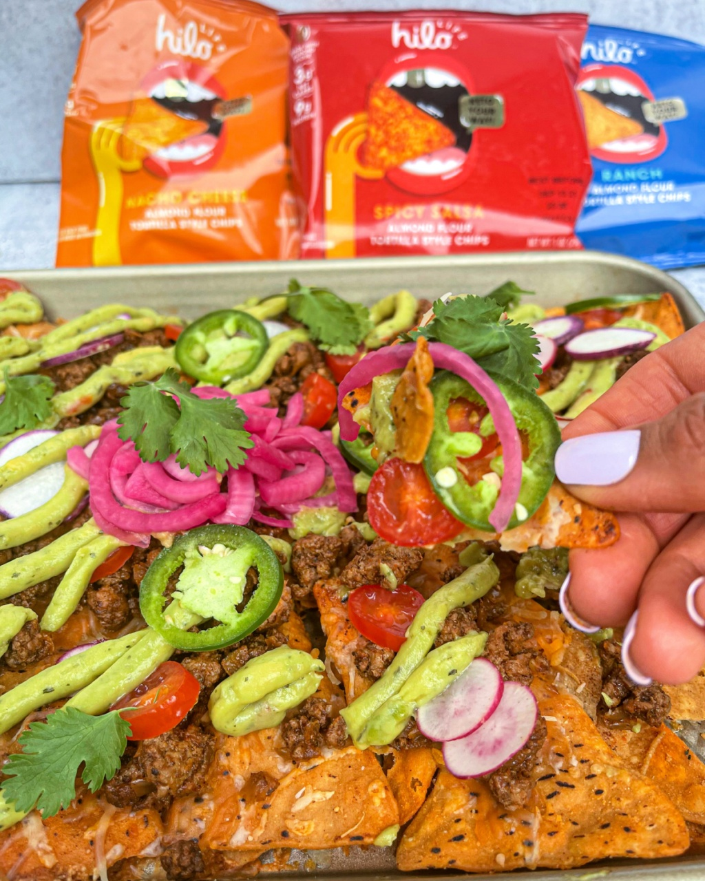 hand holding keto sheet pan nachos with HILO LIFE chips