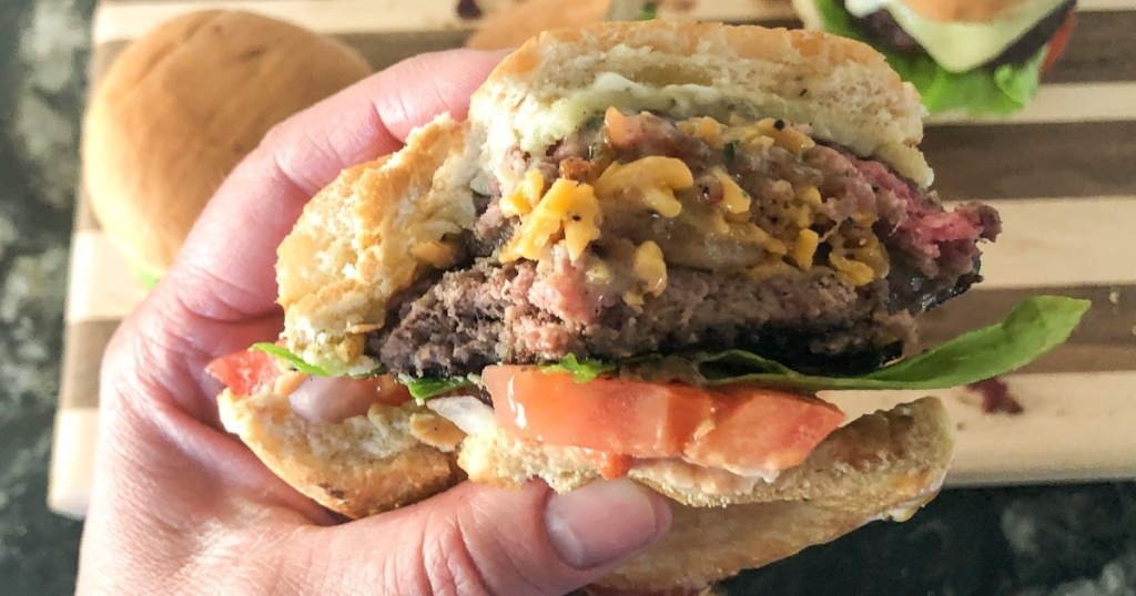 hand hold a burger with a bite out of it
