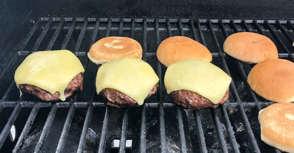burgers and buns on a grill