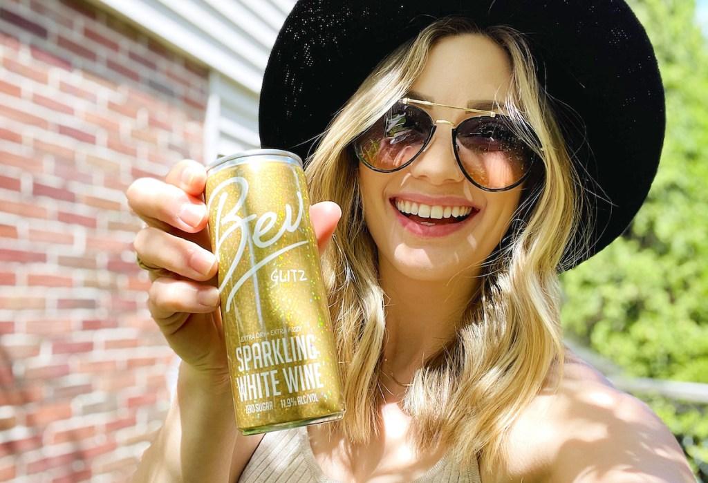 woman holding up gold bev drink