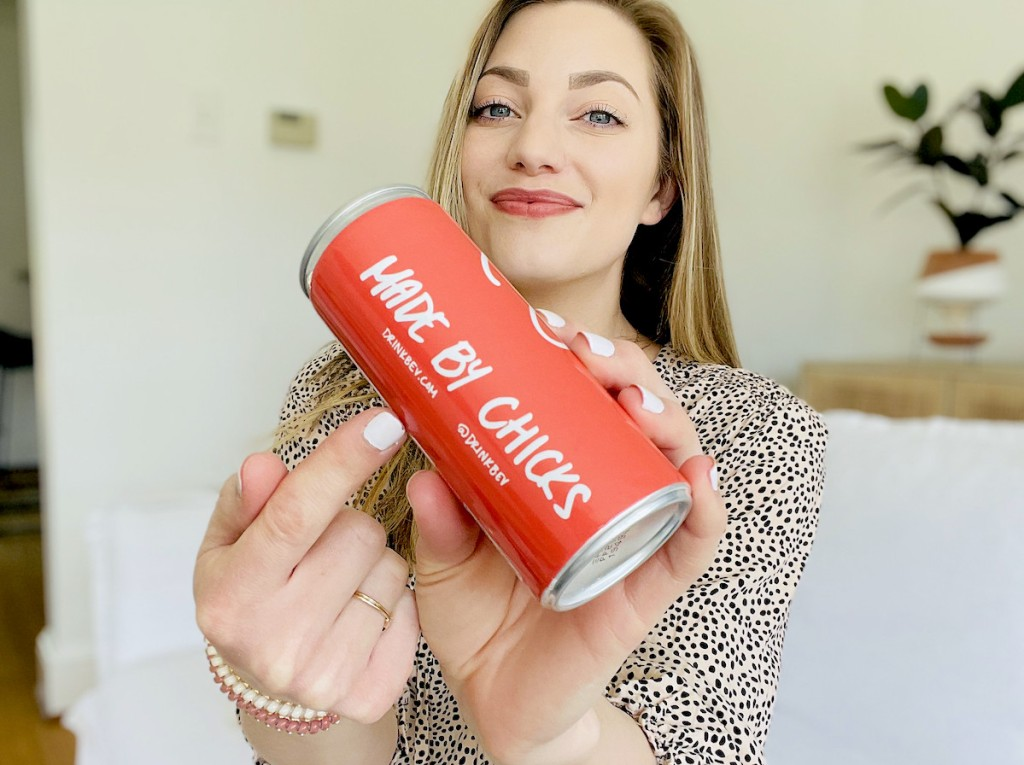woman pointing to made by chicks wording on drink