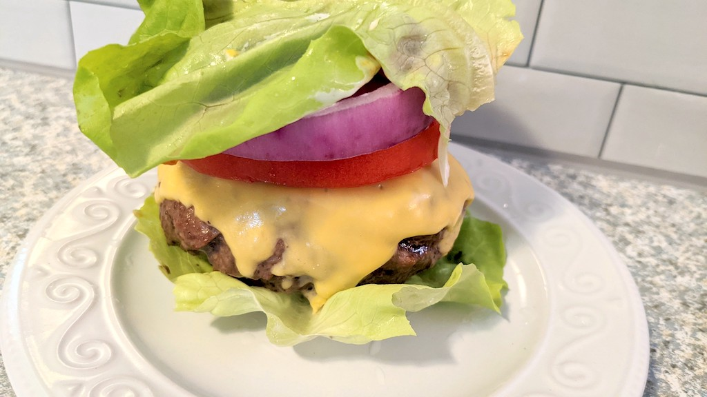 keto stuffed burgers with cheese, lettuce, tomato, and red onions