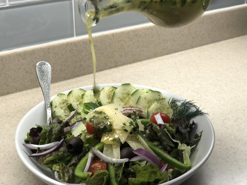 pouring pickle juice salad dressing on salad