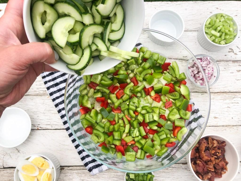 adding cucumbers to a keto salad
