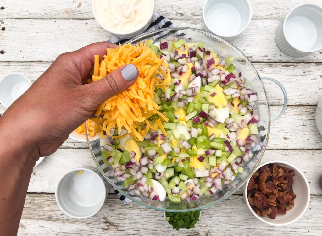 putting a handful of cheese on a keto 24 hour salad