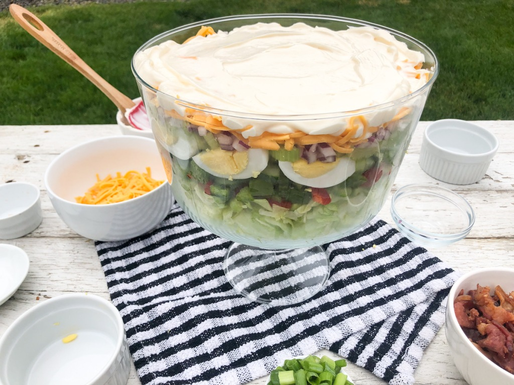 mayonnaise spread out on top of layered salad
