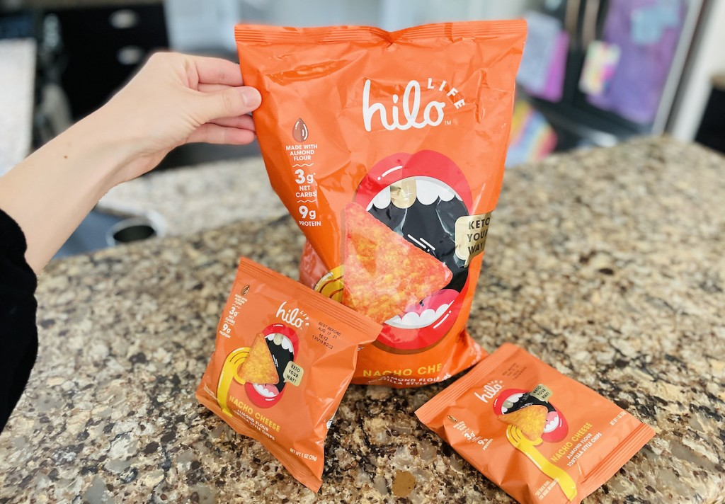 hand holding large bag of hilo chips on kitchen counter next to smaller bags