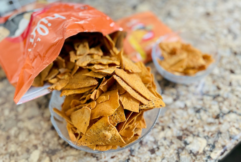 large and small bags of keto chips on granite counter spilling into clear bowls