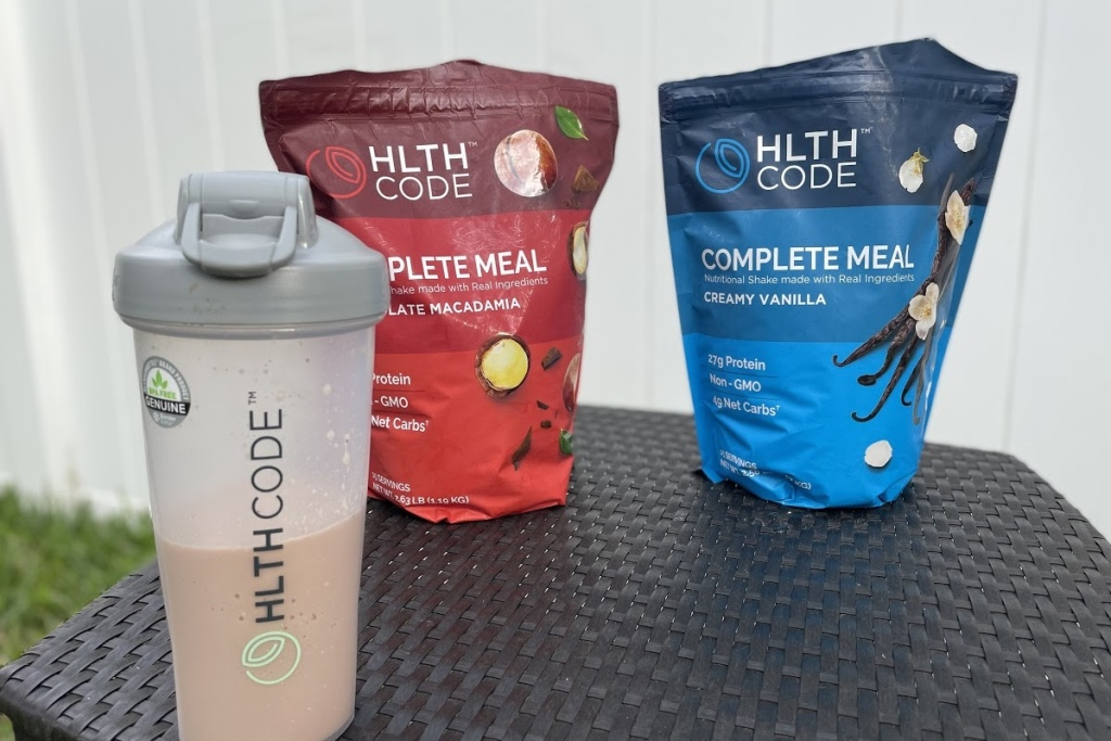 hlth code blender bottle in front of meal replacement powder bags