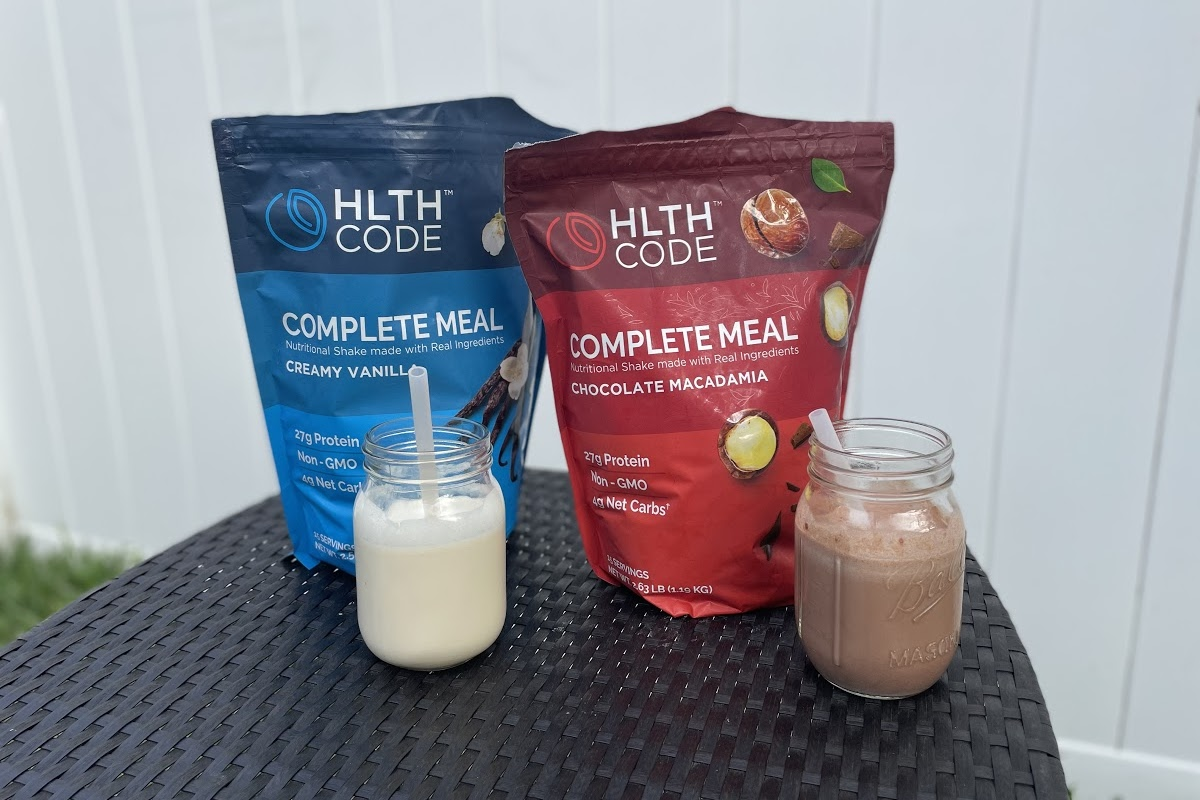 chocolate and vanilla shakes beside meal replacement powder bags on table