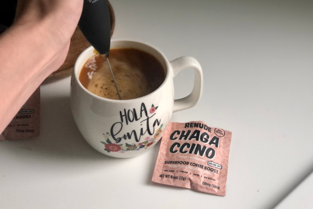 person using milk frother in a mug next to a chagaccino packet
