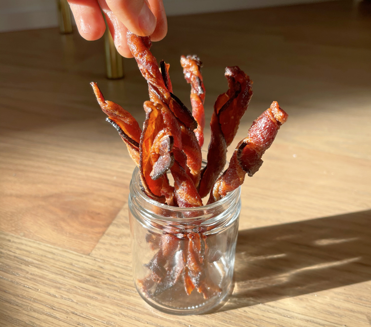 hand grabbing bacon twist out of a jar
