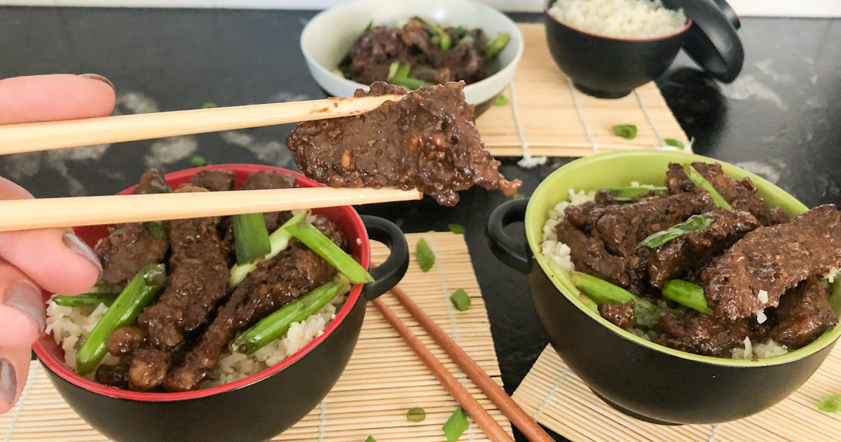 holding a piece of keto crockpot slow cooker Mongolian Beef with chopsticks