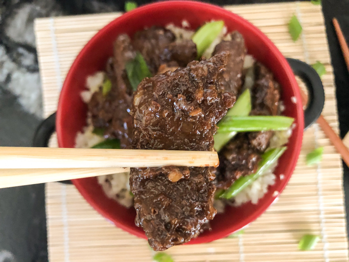 holding keto crockpot Mongolian Beef in chopsticks