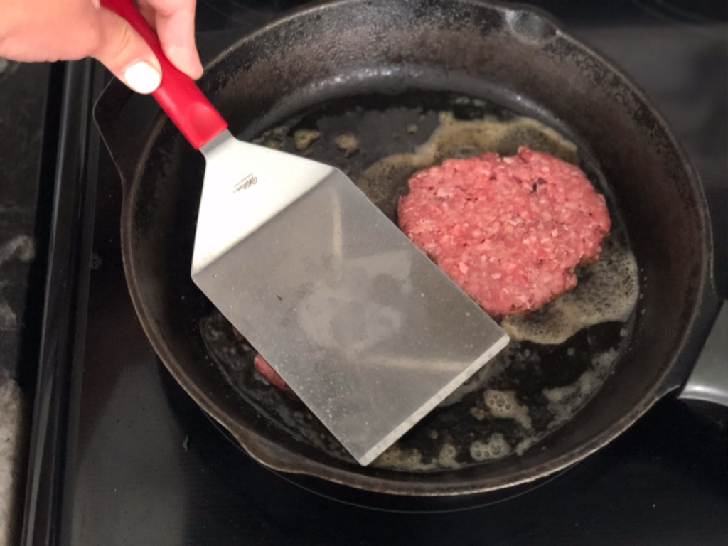 smashing burgers in a skillet